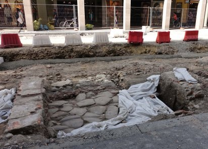A carriage wheel rut in the Roman street surface under Via Hugo Bassi.